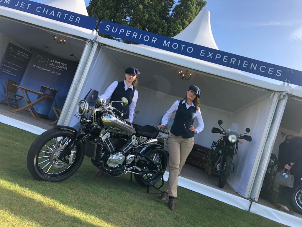 Two ladies and a Brough Superior on display stand